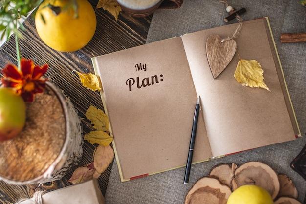 Insieme di autunno di foglie gialle e fiori e taccuino con pagine aperte sul tavolo