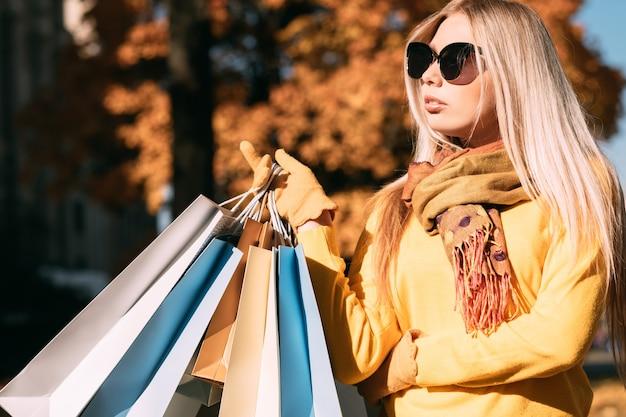 Shopping autunno elegante signora in piedi con i pacchetti, godendo la giornata di sole autunnale