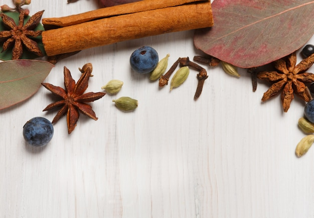 Spezie autunnali per sfondo vin brulè. cornice fatta di foglie secche ed erbe aromatiche e condimenti come cannella, cardamomo, chiodi di garofano, anice e prugnolo. vista dall'alto su legno bianco, piatto laico