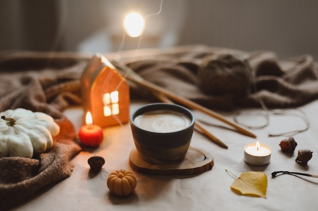 Dettagli di natura morta autunnale in interni accoglienti con una tazza, candele, plaid. arredamento per la casa hygge. concetto di halloween e del ringraziamento. banner autunnale