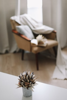 Natura morta autunnale e decorazioni per la casa in stile rustico con una tazza di libro di zucca e fiori