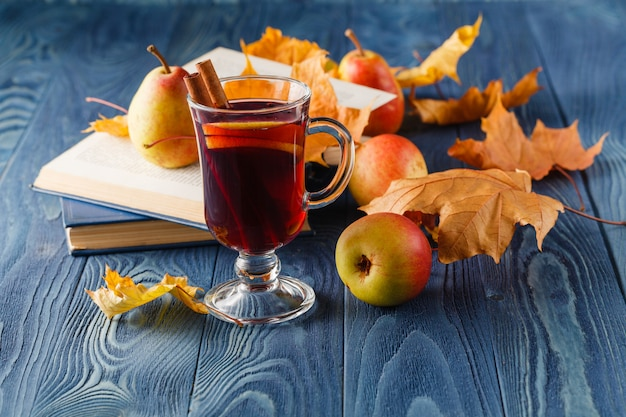Autunno still life: vin brulè con cannella, pera, foglie di autunno, libri e mela su un fondo di legno