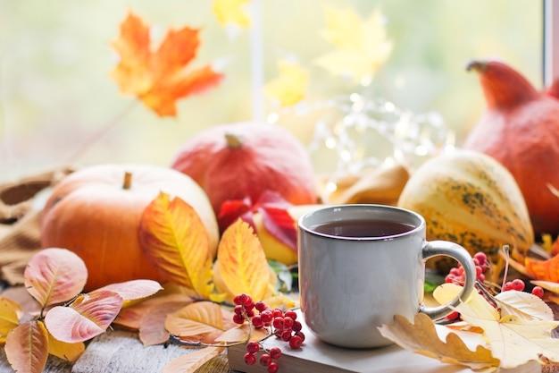 Natura morta autunnale con un bellissimo bokeh. foglie d'autunno e una tazza di caffè o tè caldo fumante, zucche arancioni stagionale, caffè mattutino, riposo domenicale e il concetto di natura morta, layout mock up