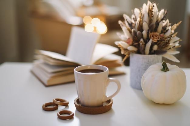 Natura morta autunnale con una tazza di caffè fiori libro e zucca hygge lifestyle accogliente atmosfera autunnale