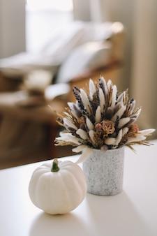Natura morta autunnale con zucca e fiori in un accogliente soggiorno soleggiato