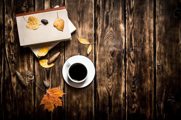 Caffè in stile autunnale con un vecchio libro su fondo in legno