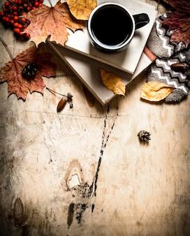 Stile autunnale. caffè con vecchi libri. sullo sfondo di legno.