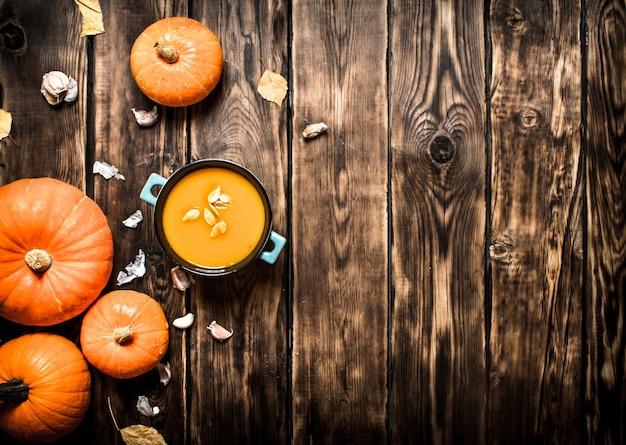 Stile di autunno zuppa di zucca fresca su fondo in legno