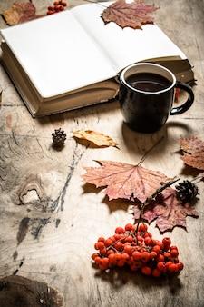 Stile autunnale. libro aperto con una calda tazza di caffè. sullo sfondo di legno.