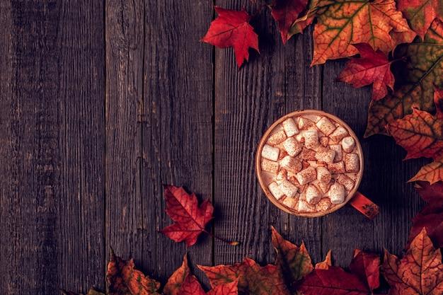 Superficie autunnale con cioccolata calda, sciarpa lavorata a maglia, foglie multicolori