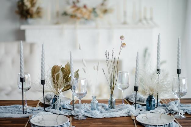 Decorazione da tavola autunnale, tavola di legno servita con fiori secchi, piatto bianco, posate vintage, candele con tovaglia di garza blu brillante. vista dall'alto, messa a fuoco selettiva.