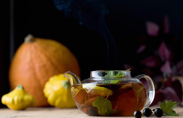 Tè autunnale con spezie al limone e bacche di ribes in una teiera sullo sfondo di zucche e squas...