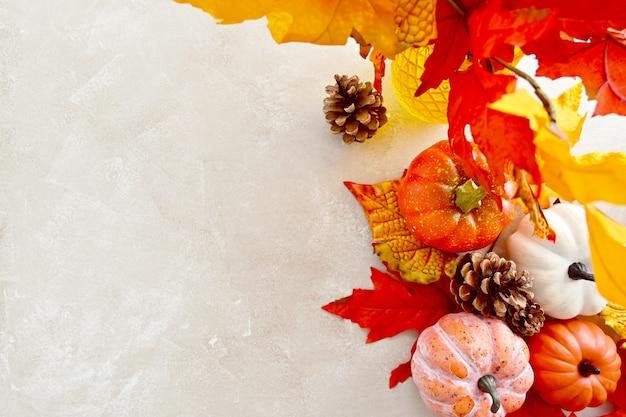 Autunno, ringraziamento, autunno sfondo astratto con foglie colorate, pigne e zucche su sfondo luminoso, copia spazio.
