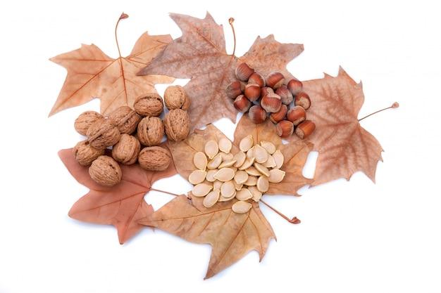 Tema autunnale con foglie gialle, noci e semi di zucca. doni della natura.