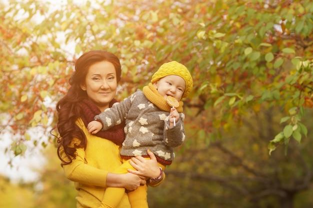 Tempo d'autunno. ritratto di una madre affascinante con la sua piccola figlia con una mela tra le braccia in un soleggiato parco autunnale caldo durante la passeggiata. luce del sole