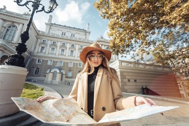 Turismo autunnale. la giovane viaggiatrice attraente è guidata dalla mappa della città. bella ragazza in cerca di direzione in città. vacanze e concetto di turismo