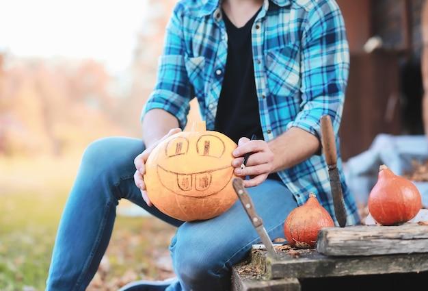 Tradizioni autunnali e preparativi per la festa di halloween. una casa nella natura, una lampada fatta di zucche si ritaglia a tavola.
