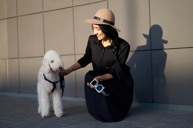 Collezione autunno alla moda. bella ragazza felice del brunette che porta vestito grigio alla moda che tiene cappello alla moda nelle mani. modello in abito alla moda in posa su sfondo grigio muro. ritratto all'aperto.