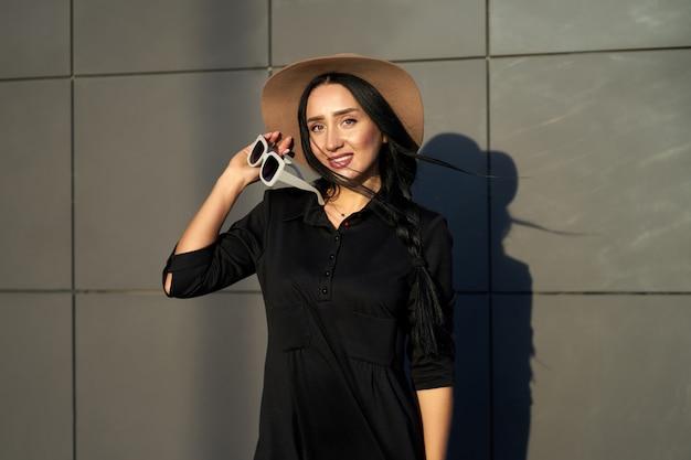 Collezione autunno alla moda. bella ragazza felice del brunette che porta vestito grigio alla moda che tiene cappello alla moda nelle mani. modello in abito alla moda in posa sul muro grigio. ritratto all'aperto.
