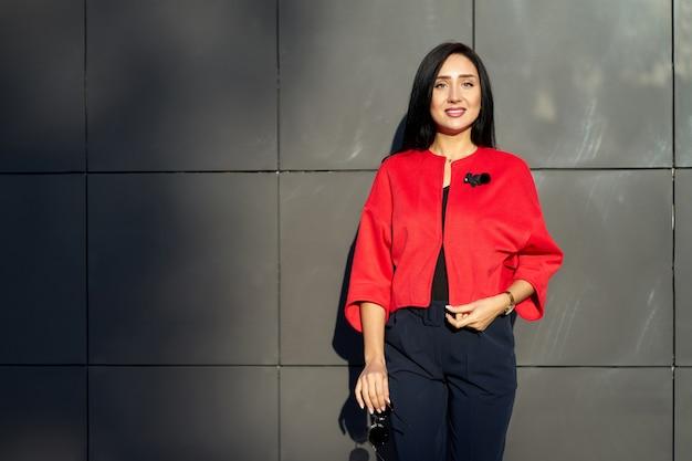 Collezione autunno alla moda. giovane ragazza attraente in occhiali da sole alla moda che indossa giacca rossa elegante e pantaloni blu sulla parete grigia