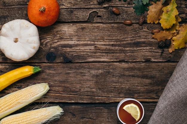 Verdure autunnali: tè, zucche e mais con foglie gialle su legno