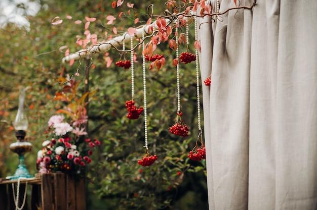 Matrimonio autunnale in strada sul prato verde.decorazione con archi di fiori freschi per la cerimonia.