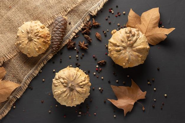 Autunno inverno sfondo con zucche, foglie secche e tavolo rustico