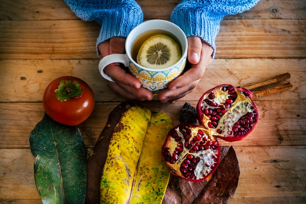 Immagine di concetto freddo autunnale e invernale con vista dall'alto di un tavolo rustico in legno e mani di persone che tengono una tazza di tè calda