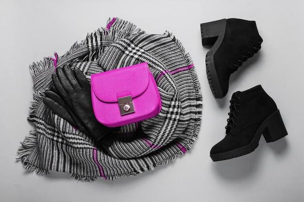 Accessori donna autunno. sciarpa femminile alla moda, stivali, borsa rosa, guanti su sfondo grigio. vista dall'alto. lay piatto