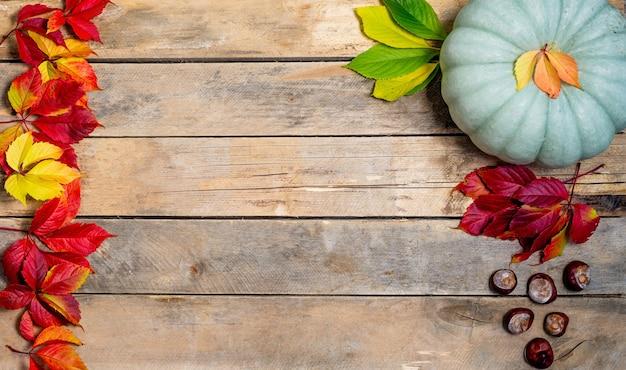 Autunno in legno con foglie giallo-rosse e verdi, zucca e castagna.