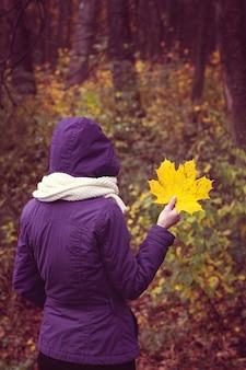 Foglia gialla autunnale nelle mani di una ragazza