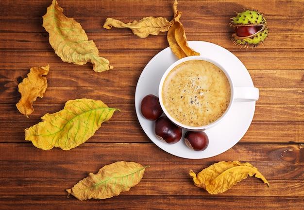 Foglie gialle d'autunno, castagne e tazza di caffè su fondo di legno.