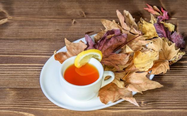 Tè caldo autunnale con limone, mucchio di foglie secche di caduta sul piatto bianco e tavolo in legno