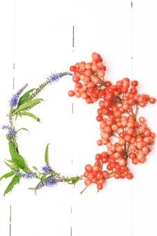 Natura morta autunnale della cornice rotonda della corona. fiori autunnali, mele, cenere di montagna