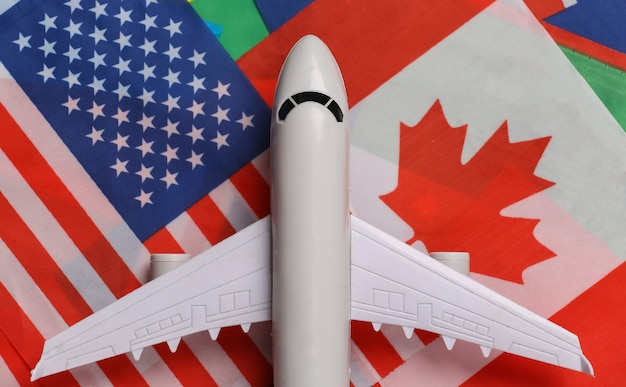 Tema di viaggio avia. la figura di un aereo passeggeri sullo sfondo di molte bandiere di paesi