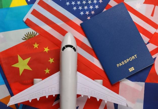 Tema di viaggio avia. la figura di un aereo passeggeri, passaporto sullo sfondo di molte bandiere di paesi