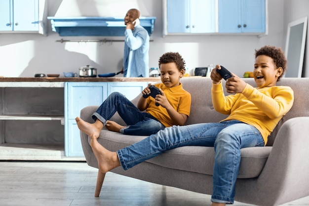 Giocatori accaniti. allegri ragazzini seduti sul divano e immersi nella riproduzione di un videogioco con i controller mentre il padre cucina per loro in sottofondo