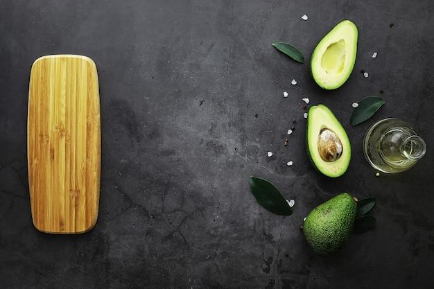 Ricette di cucina con avocado. avocado verde maturo su un tagliere di legno per servire.