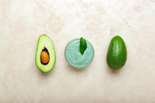 Maschera viso avocado in vaso di vetro con foglie e avocado
