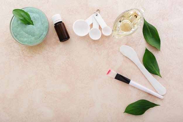 Maschera viso di avocado, spatola, pennello, misurini, olio, olio essenziale su sfondo rosa chiaro