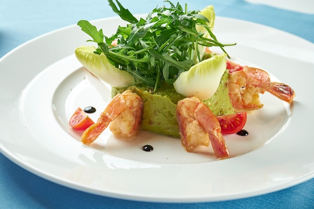 Guacamole di avocado con gamberetti, rucola e pomodorini in un piatto bianco sulla tovaglia blu. avvicinamento. cibo messicano