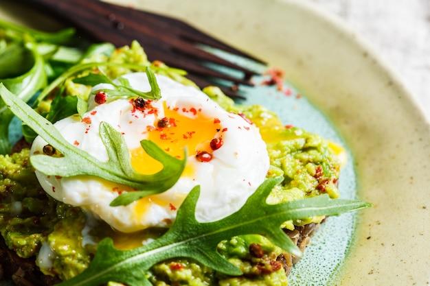 Toast di avocado e uovo in camicia su pane di segale. concetto di sana colazione.