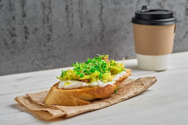 Sandwich di avocado con crema di formaggio, microgreens e semi di sesamo su rivestimento di carta. avvicinamento.