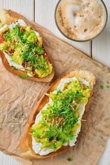Sandwich di avocado con crema di formaggio, microgreens e semi di sesamo su rivestimento di carta. vista dall'alto. tazza con cappuccino, fuoco selettivo. concetto di colazione o brunch. toast vegetariano