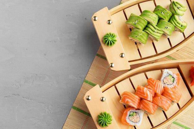 Avocado sushi roll and roll con salmone servito su piatti di legno si chiuda