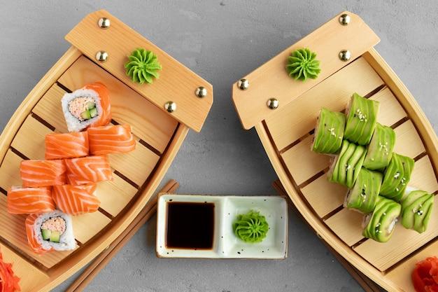 Avocado sushi roll and roll con salmone servito su piatti di legno