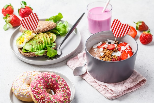 Toast di avocado e ciambelle rosa su sfondo bianco