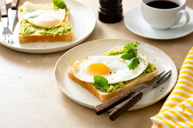 Toast di avocado con uova fritte e piselli freschi, tazzine da caffè. colazione sana, cibo cheto. concetto di dieta.