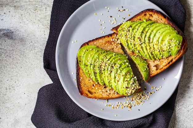 Toast di avocado con semi di canapa su lastra grigia