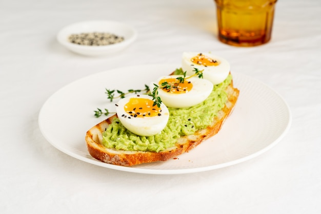 Toast di avocado con pane tostato, uova alla coque alle erbe